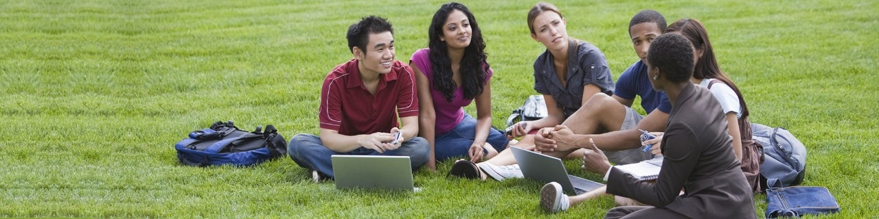 College students and a teacher learning outside on the grass