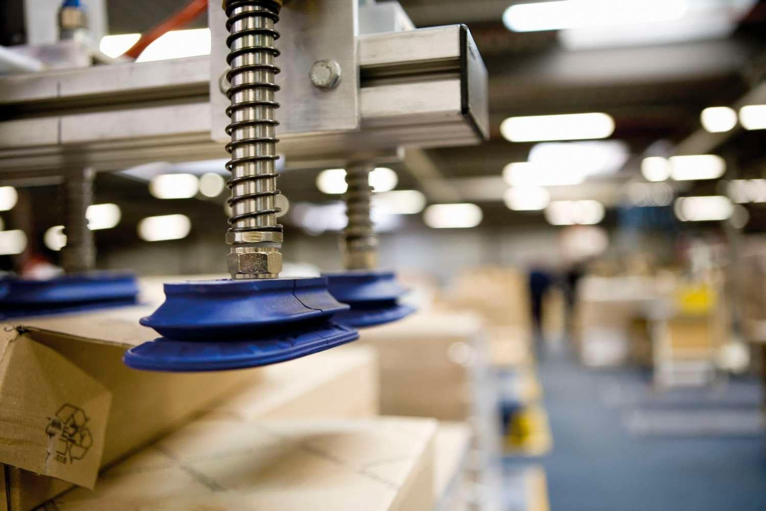 Pneumatic robot arm lifts boxes in a warehouse