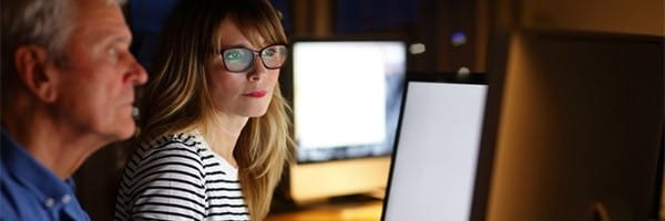 Two people reviewing information on a desktop computer.