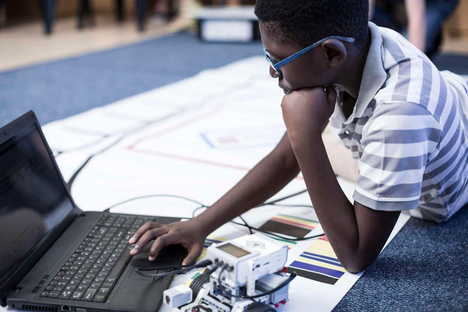 Young male student programming robotics from a laptop