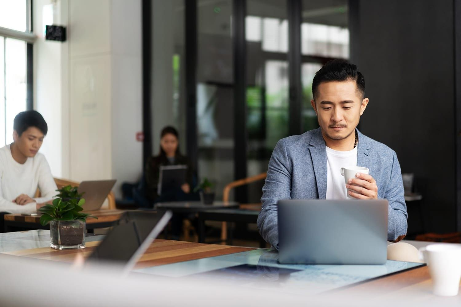 Young asian male with laptop and coffee mug