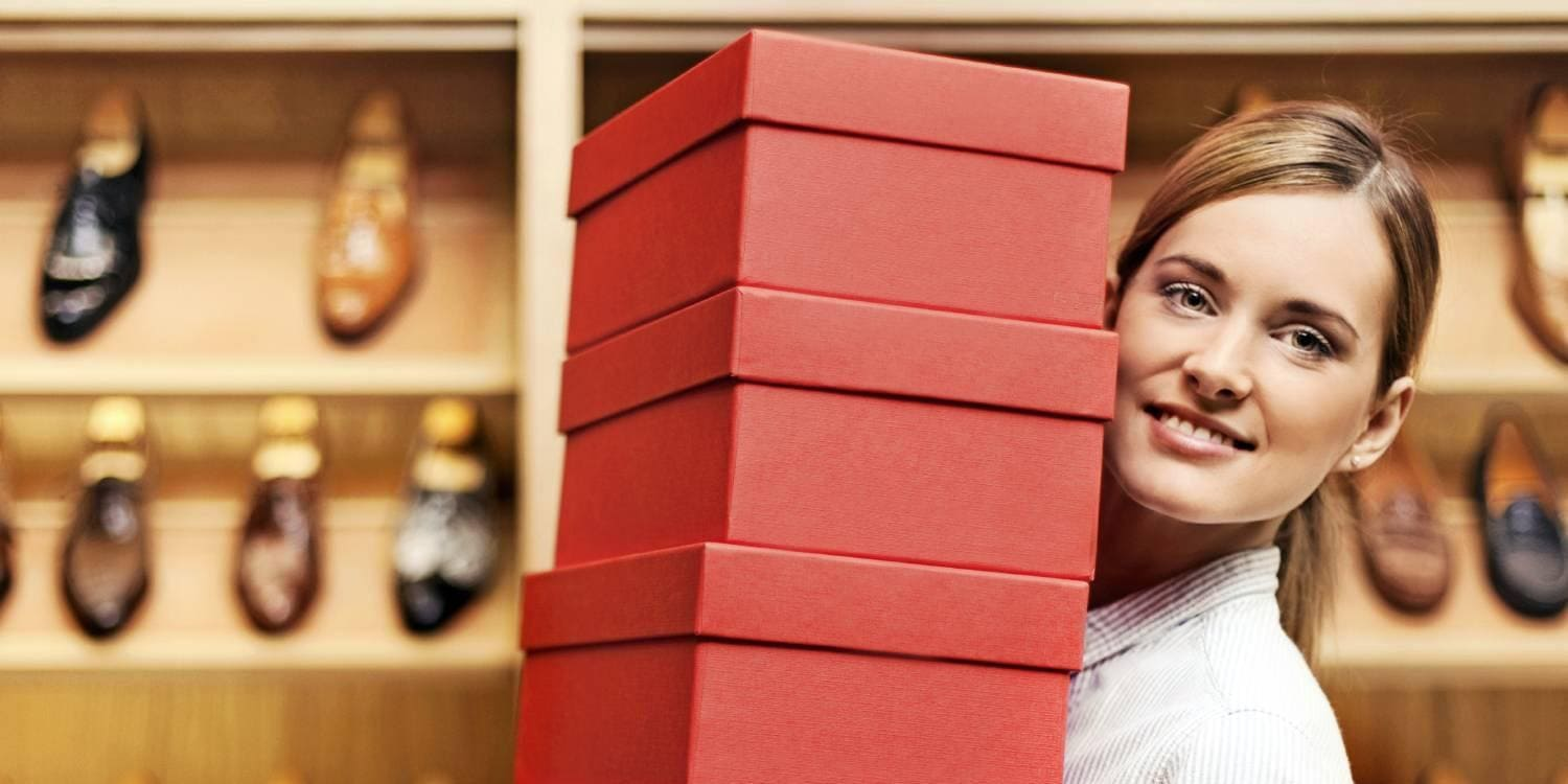 Woman carrying shoe boxes in shoe store