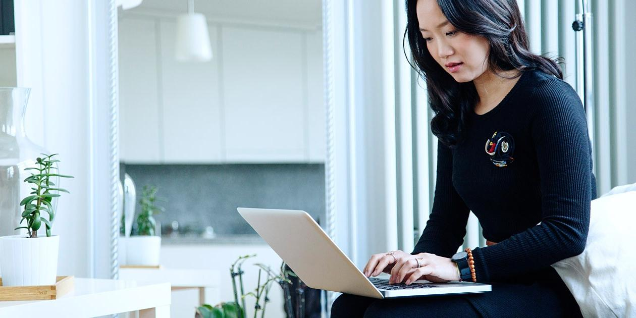 Businesswoman holding laptop on lap and typing
