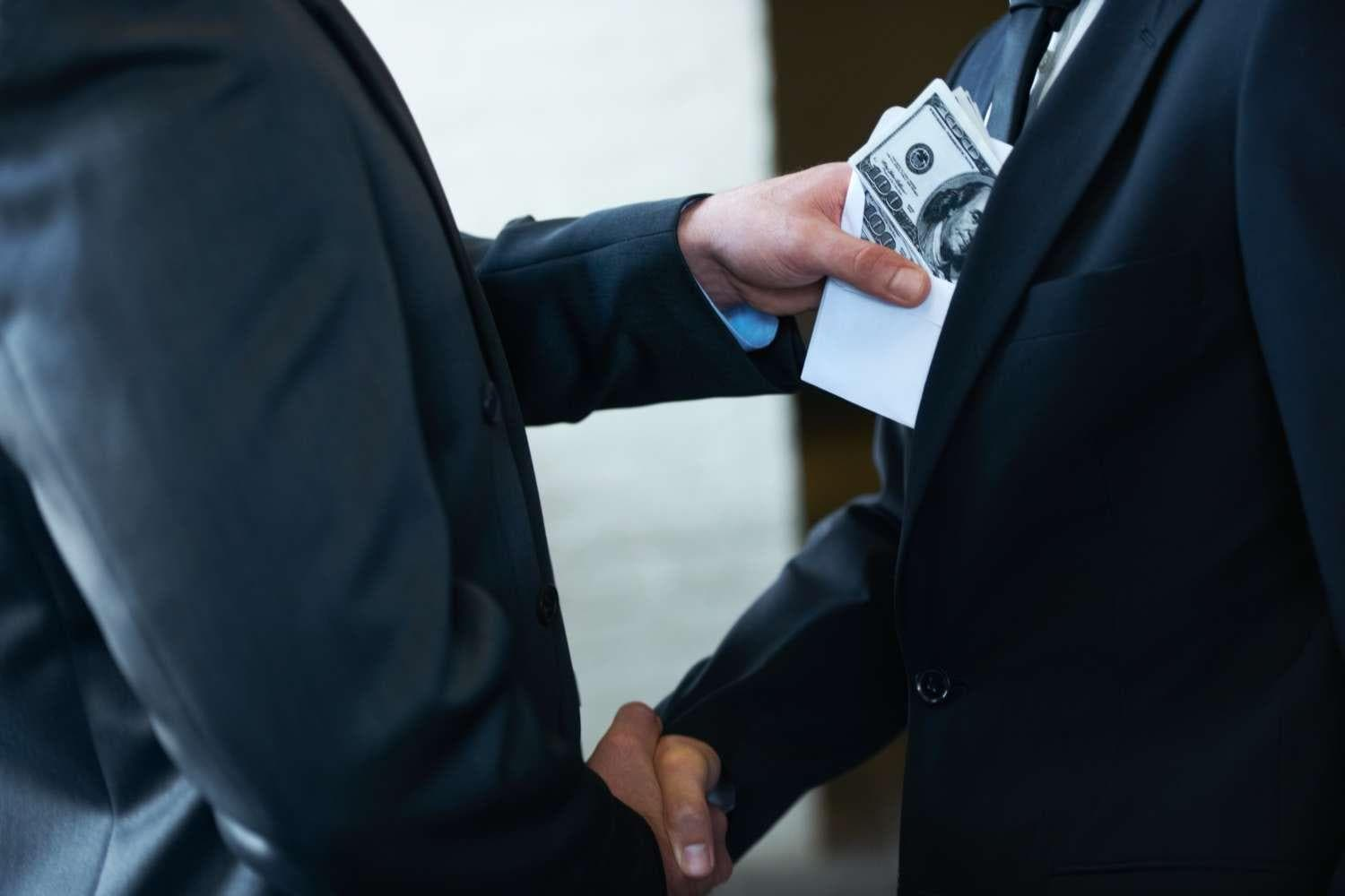 Two corporate businessmen shaking hands while one man places money in the other