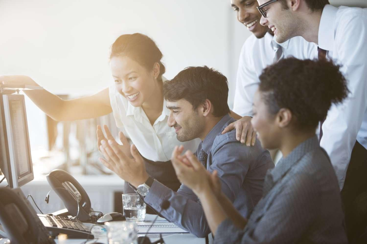 Business people cheering at computer in office