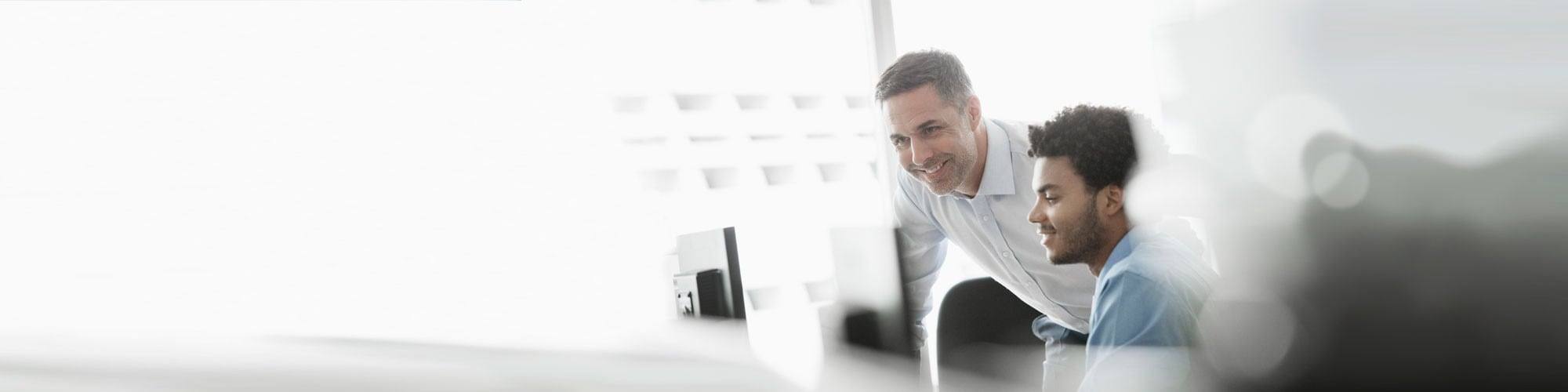 Two business professionals looking at computer