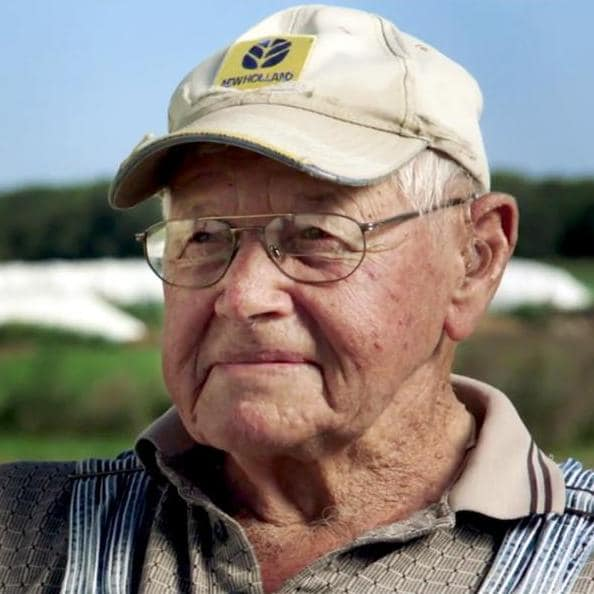 George Lauderdale smiling at camera on the farm
