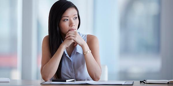 millenial asian woman pensive notebook