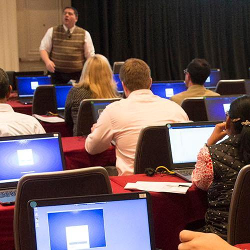 People sitting at tables with laptops in a training session listening to speaker