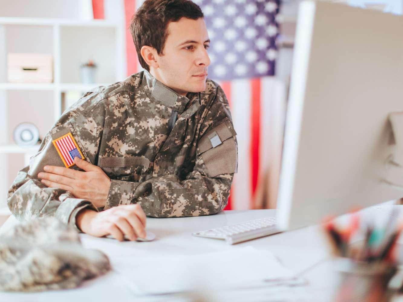 Man in military uniform working on desktop computer