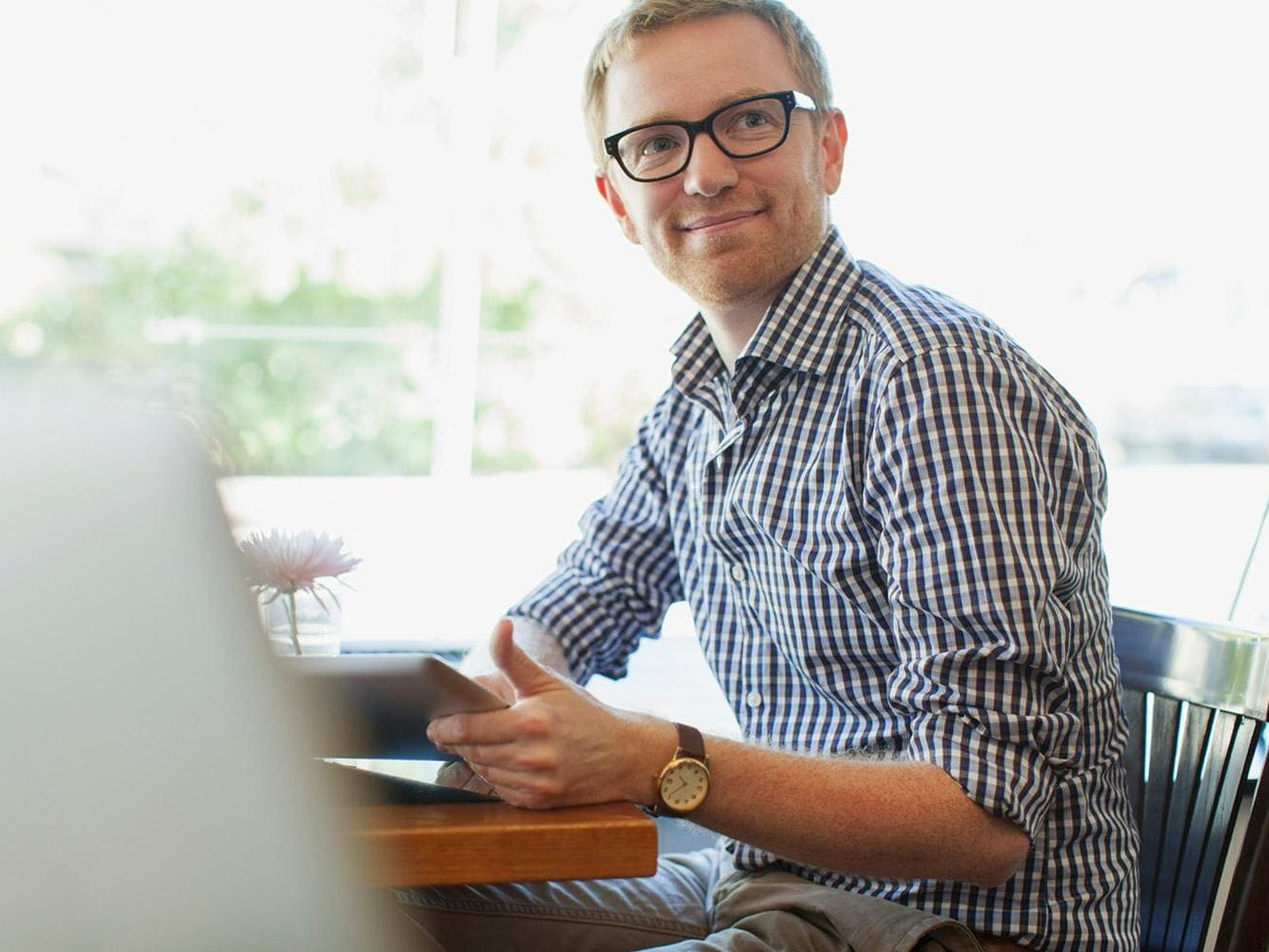 Man smiling towards camera and working on tablet