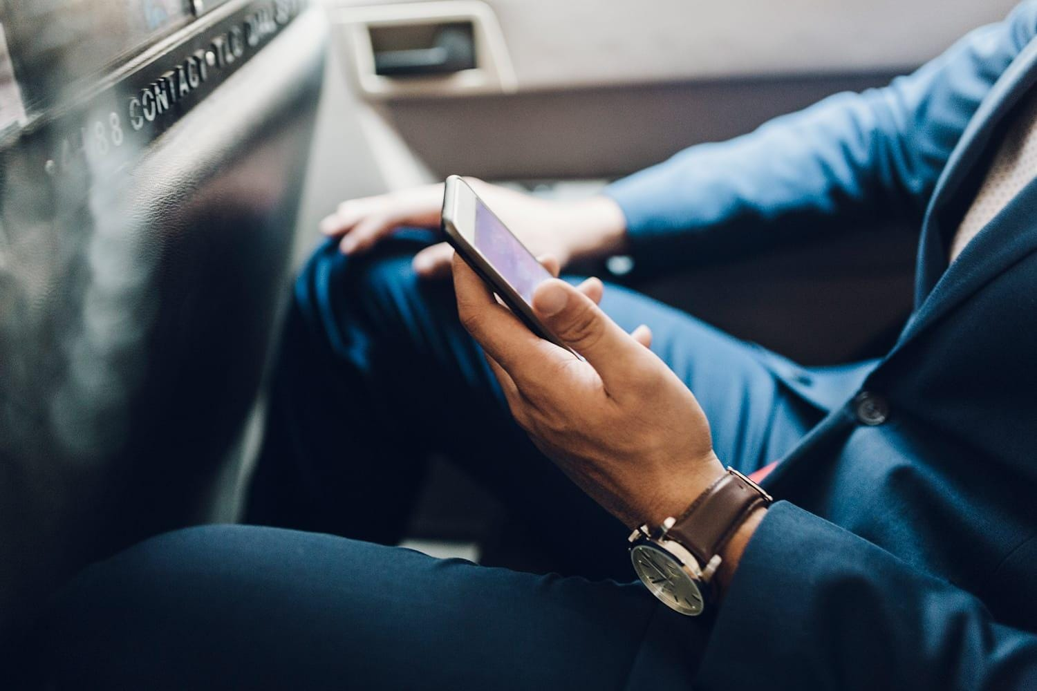 Close up of businessman with mobile phone in taxi
