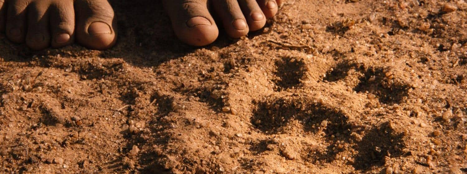 Namibian girl looking at footprints in the sand