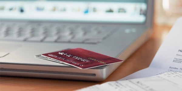 Credit card laying on the corner of an open laptop