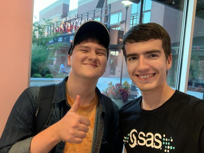 Two neurodiverse interns smiling at camera and giving thumbs up