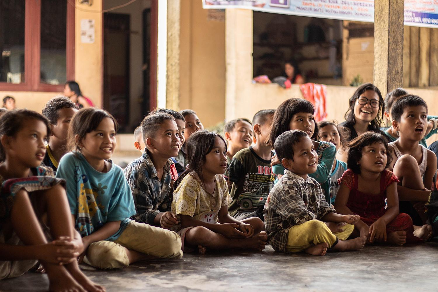 Children in poverty sitting and listening to story