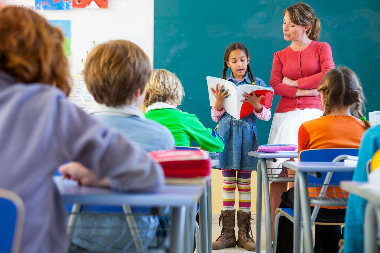 Young student reading aloud at front of classroom with teacher