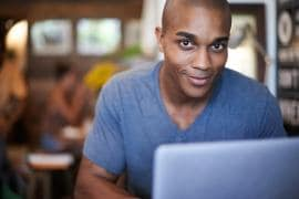 young man using his laptop in a coffee shop
