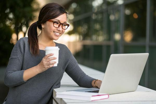 Lady outside on laptop with coffee