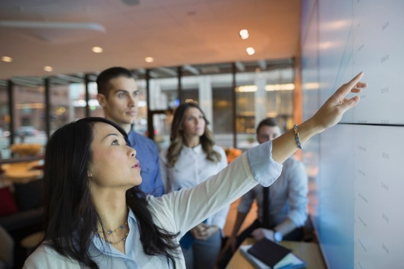 Business people pointing at projection screen