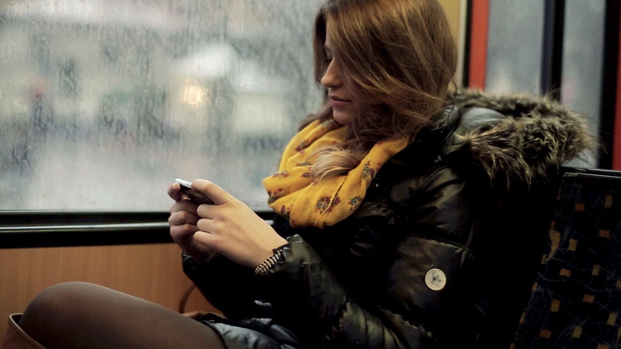 Woman sitting beside window looking at mobile device.