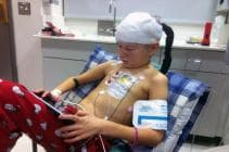 Young boy with cancer in hospital bed playing on a tablet