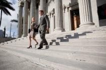 Businessman and Businesswoman walking down stairs of government building