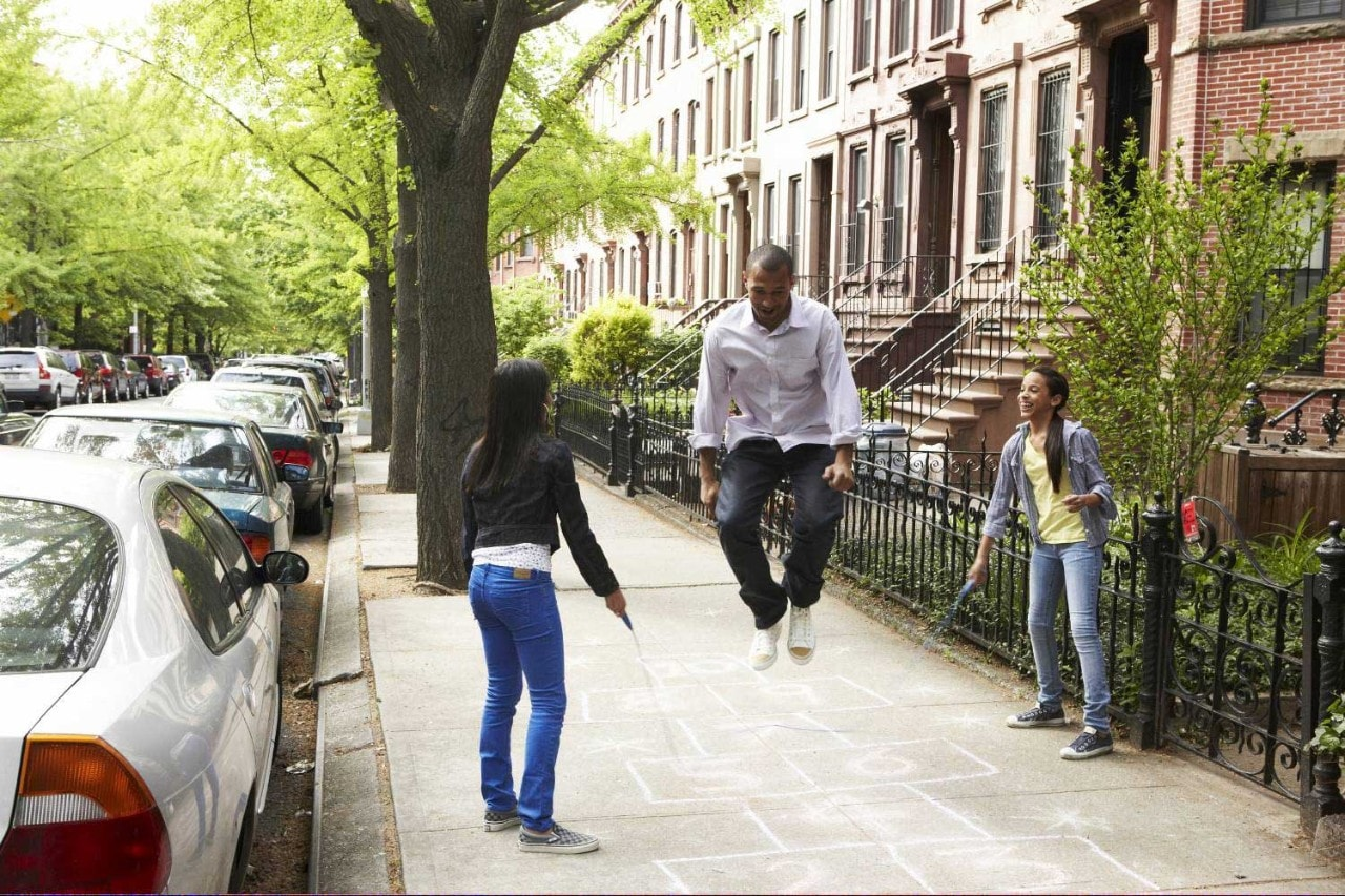 family jumping rope on city sidewalk