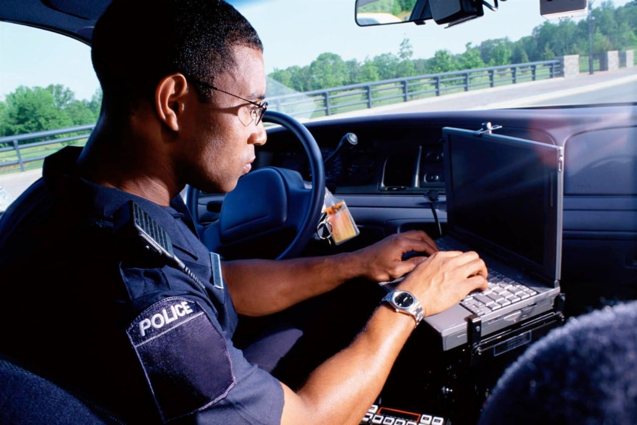 police officer parked in car on laptop