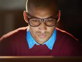 Young black man with computer on dark background
