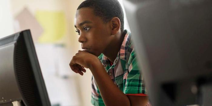 Young male student looking at desktop computer