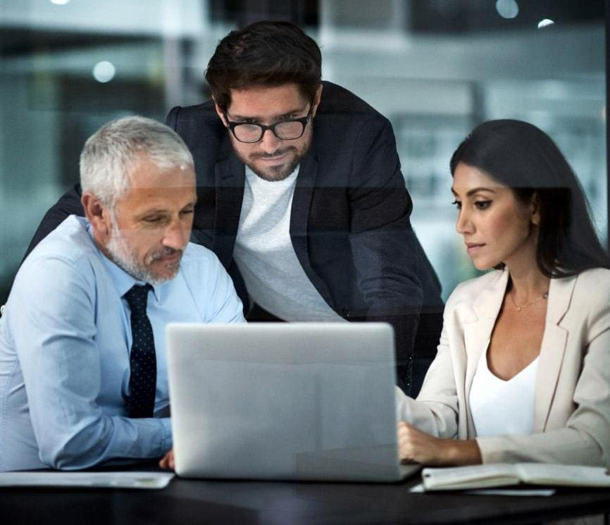 Trio of business people looking at laptop