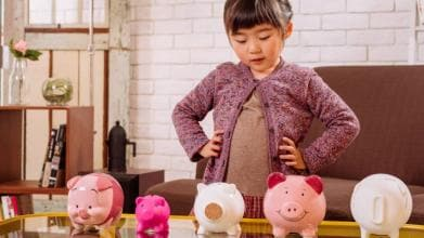Little girl thinking in front of piggy banks