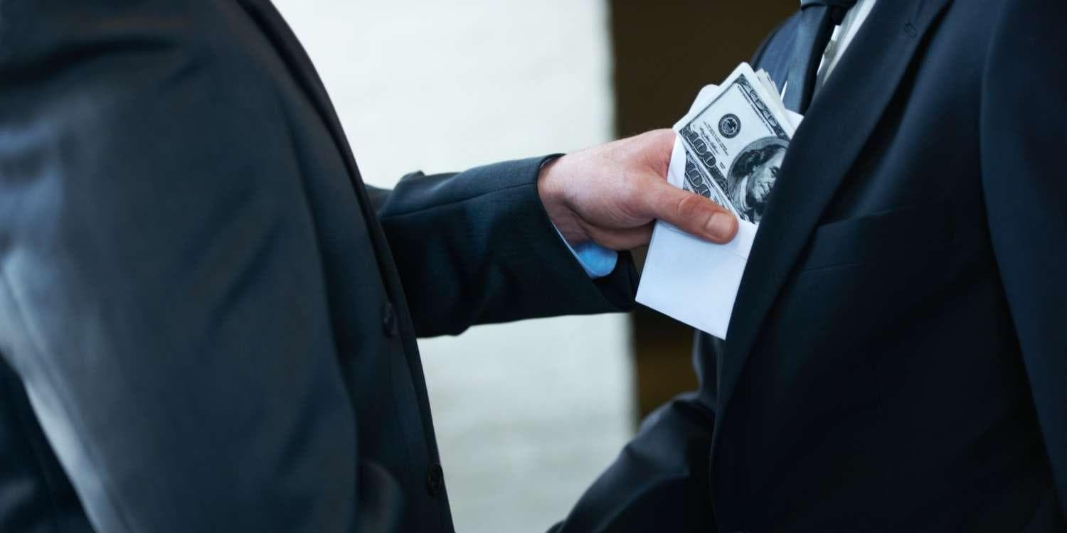 Two business men shaking hands and holding cash