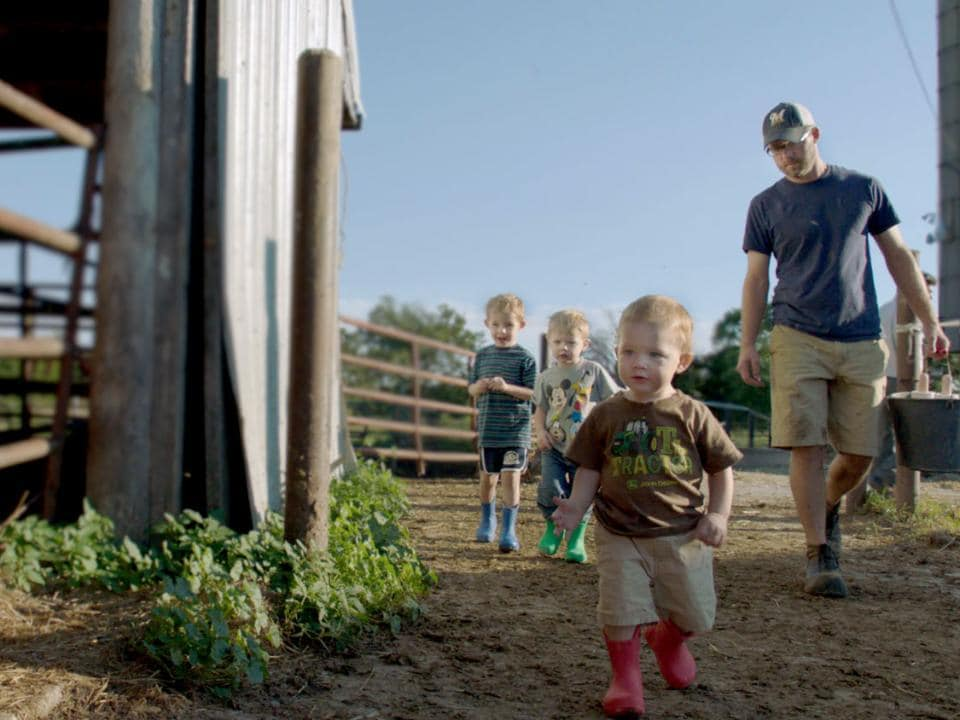 Dan Lauderdale and three sons walking on farm