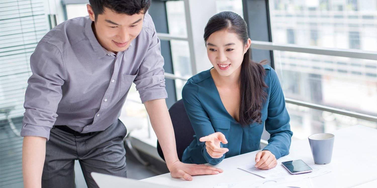 Young asian business man and woman discuss data on laptop computer