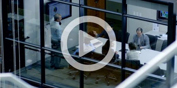 Business people, seen through office building window, discussing visual analytics