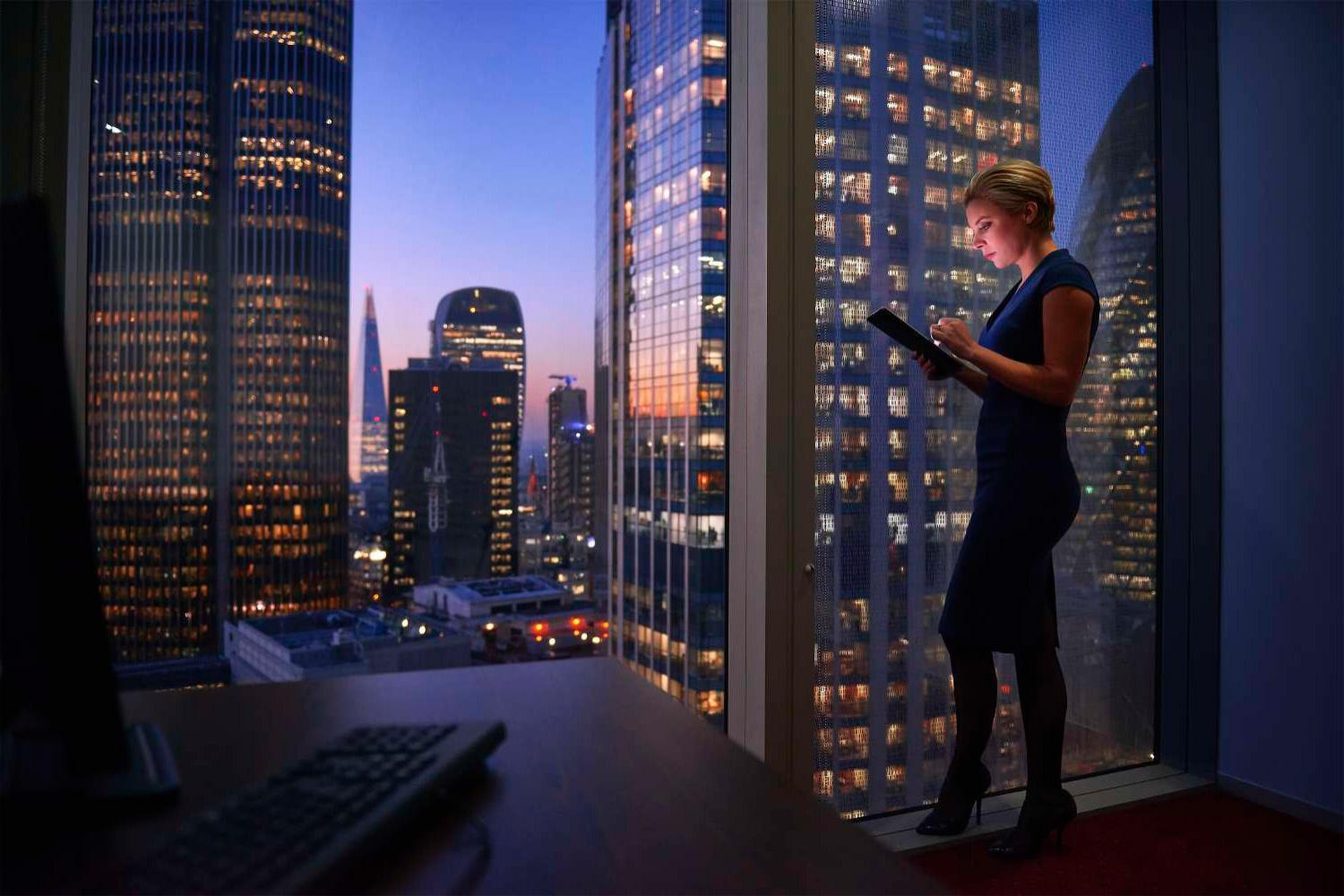 Blond woman on tablet in front of cityscape
