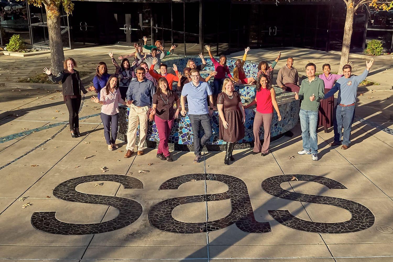 SAS employees standing behind ground logo