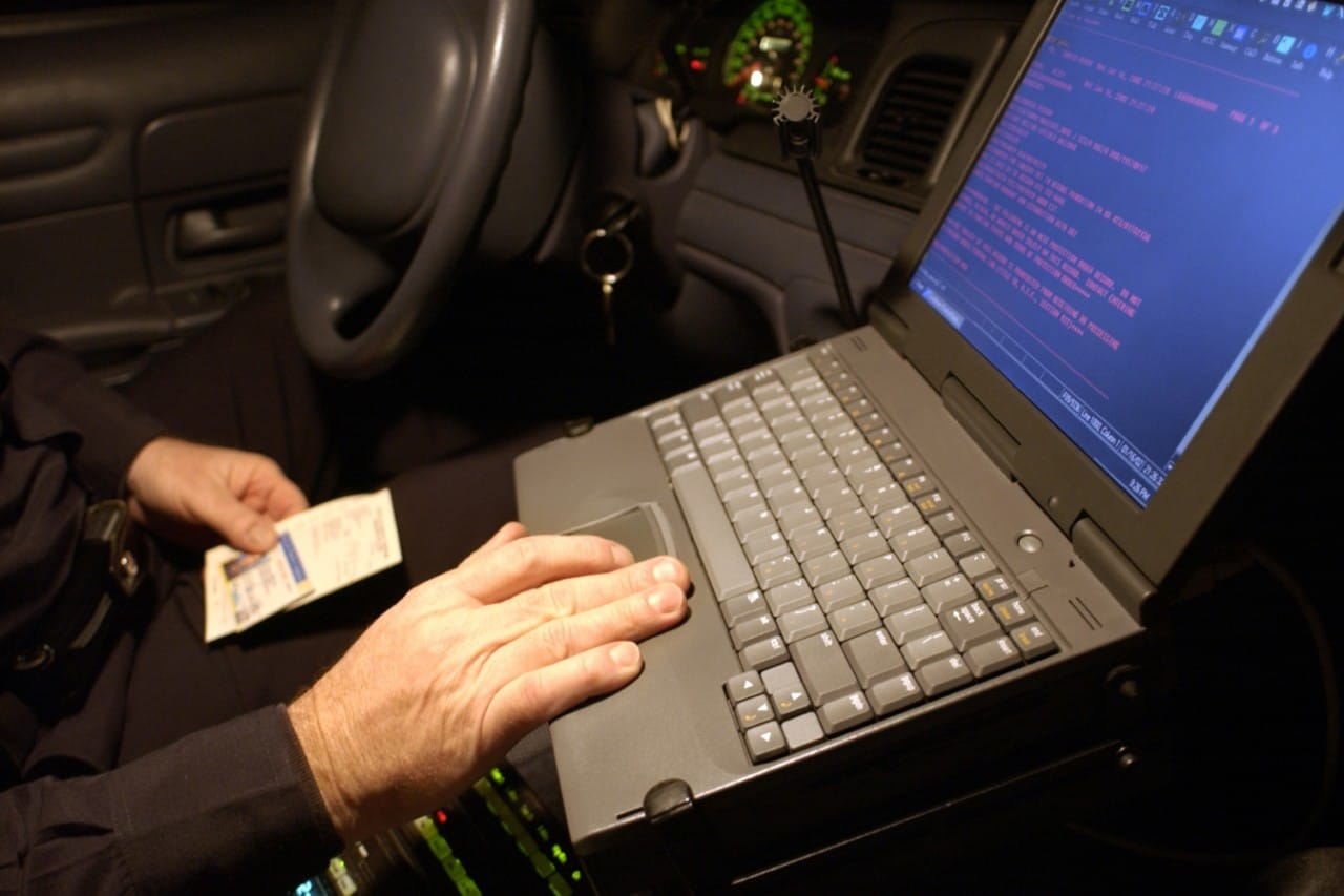 police officer using laptop in patrol car