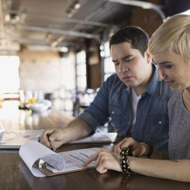 Two business partners working on paperwork next to laptop
