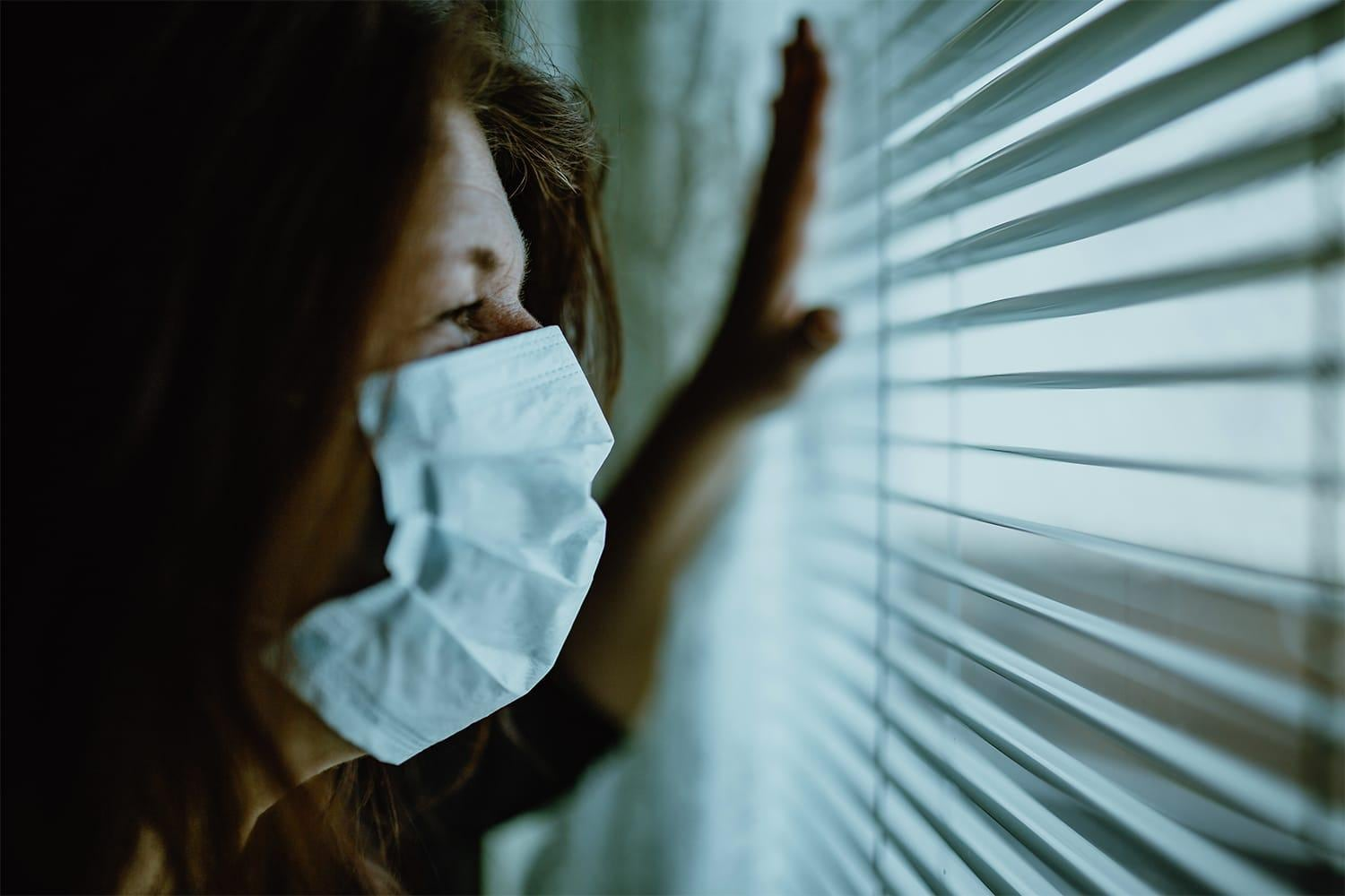 Woman with mask looking out window