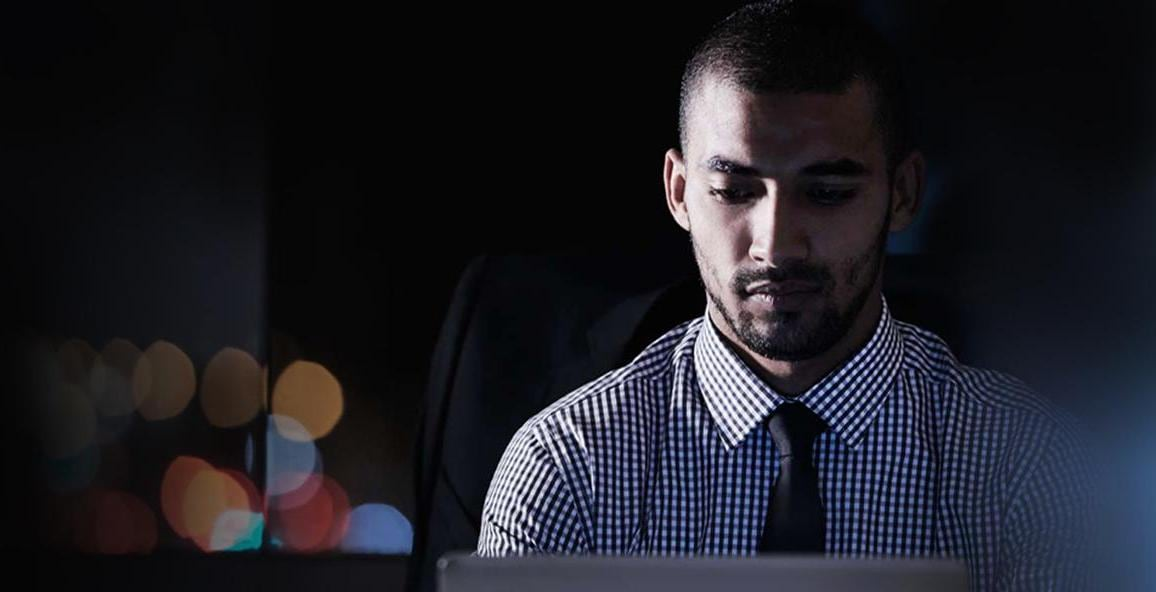 Man with tie on laptop at night