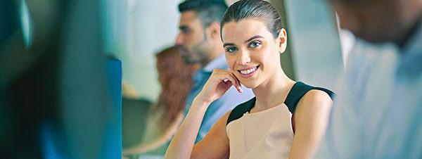 Young woman sitting at keyboard and looking at camera