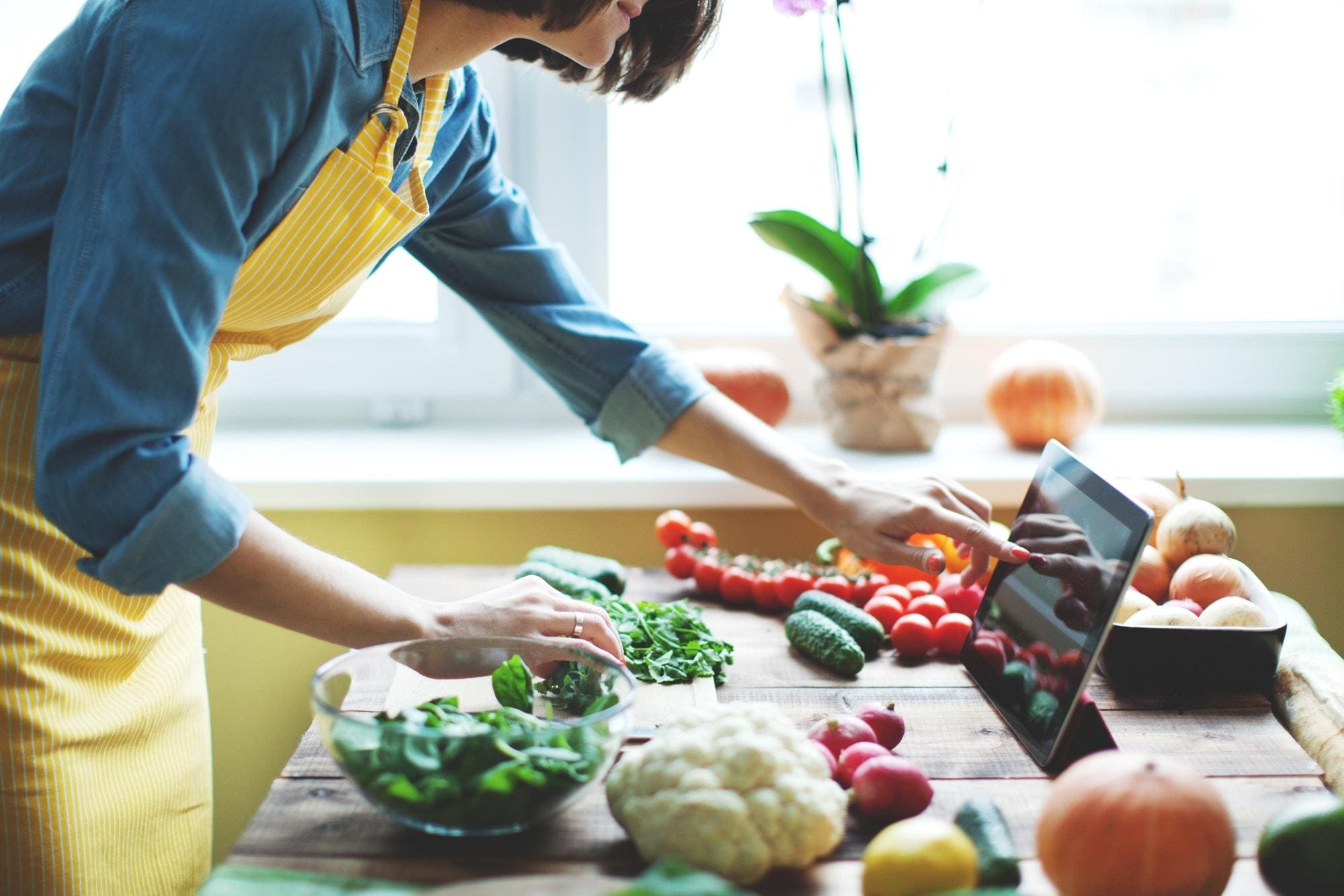 Woman touching tablet while cooking with vegetables in kitchen