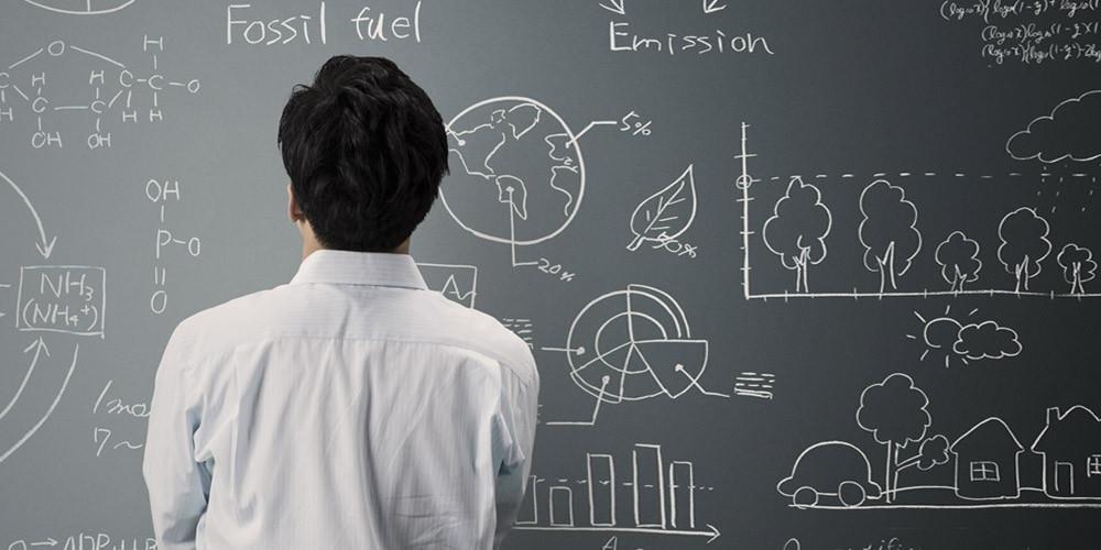 Man looking at blackboard of data