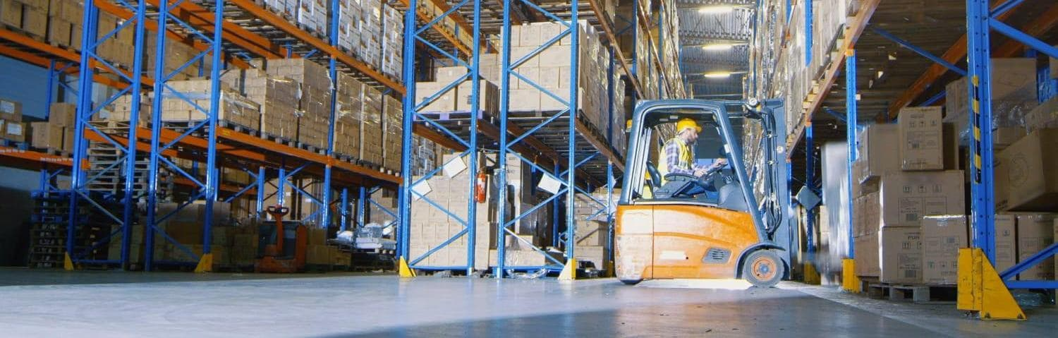 Man driving lift truck in warehouse
