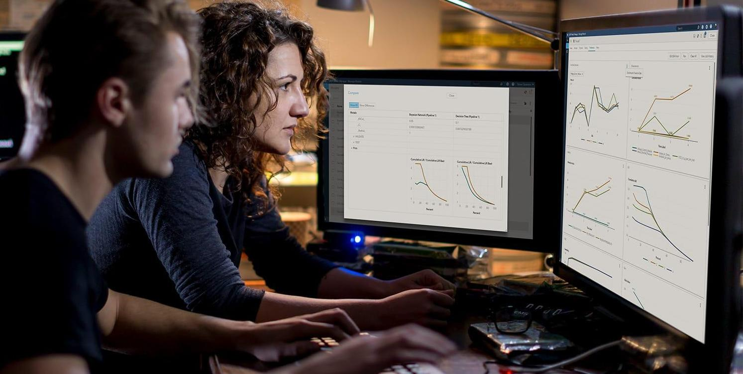 Two young professionals study data on desktop computers using SAS® Model Manager