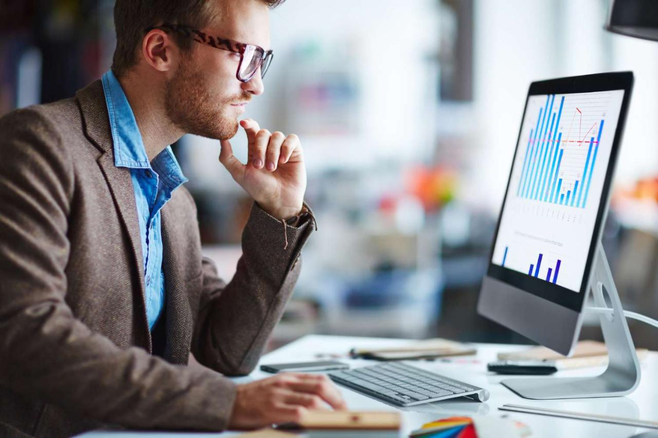 Looking at monitor -- male office worker looking at computer screen with data