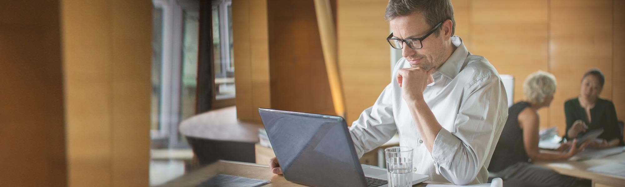 Man shown working on laptop at desk